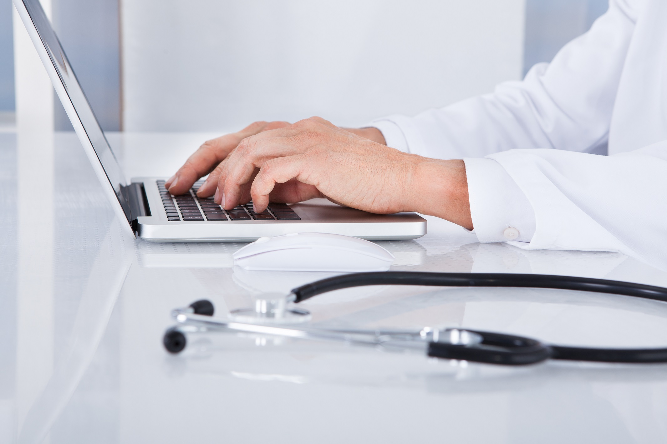 Close-up Of Doctor Using Laptop In Front Of Stethoscope At Desk